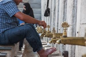 A man performing Wudu, a ritual washing